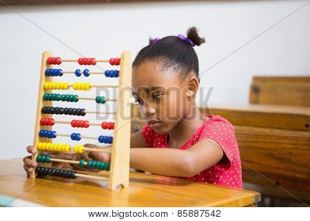Cute pupil using abacus in classroom at the elementary school