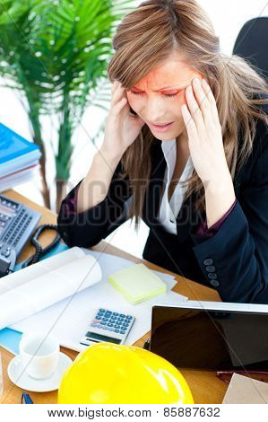 Stressed businesswoman having a headache in the office