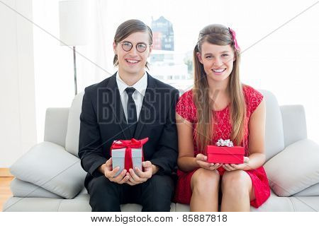 Cute geeky couple smiling and holding gift on the couch