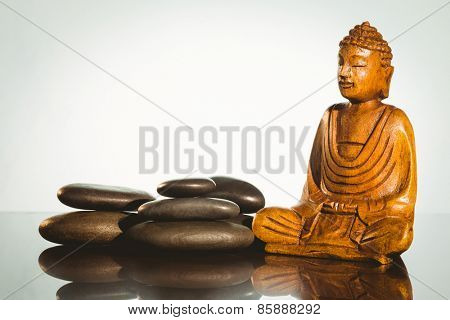 Wooden buddha statue with balancing pebbles shot in studio