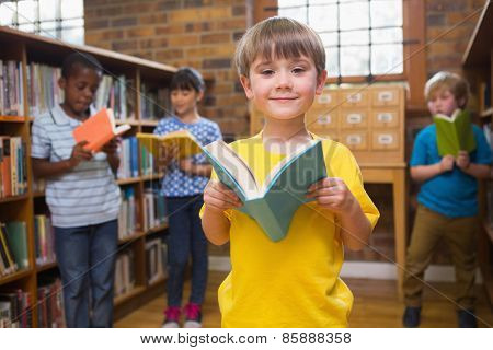 Cute pupils reading books at library at elementary school