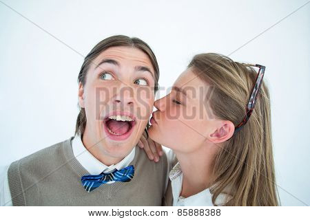 Pretty geeky hipster giving boyfriend kiss on the cheek on white background