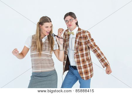 Happy geeky hipsters singing with microphone on white background