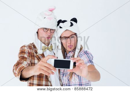 Geeky hipster couple taking selfie with smart phone on white background