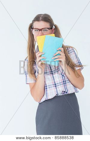Geeky hipster hiding her face behind notepad on white background