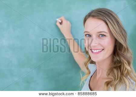 Smiling teacher writing on blackboard in classroom