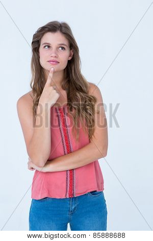 Thoughtful woman with finger on chin on white background