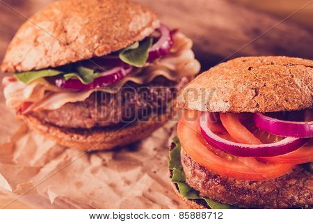 Two Burgers Close Up On A Cutting Board. Vintage Style.