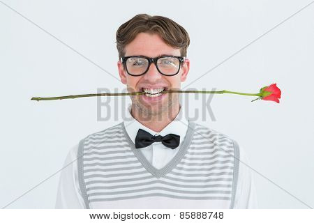 Geeky hipster holding a red rose in his teeth on white background