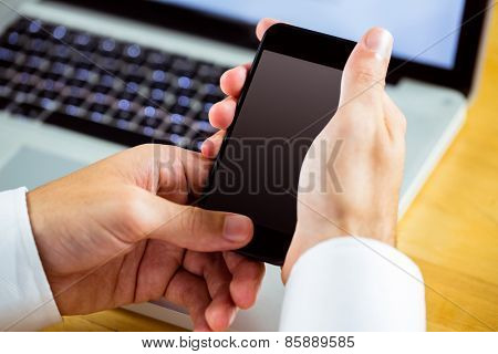 Man using laptop and smartphone in close up