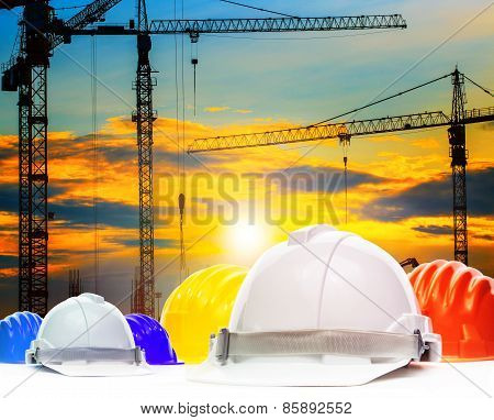 Safety Helmet And Structure Of High Crane In Construction Site Against Beautiful Evening Sky Use For