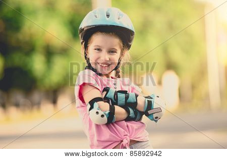 beautiful girl on the rollers in helmet and protection