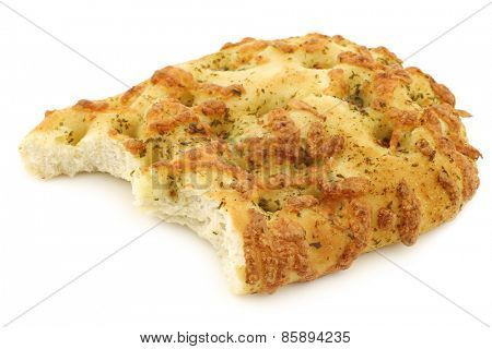 freshly baked focaccia bread with a bite missing on a white background