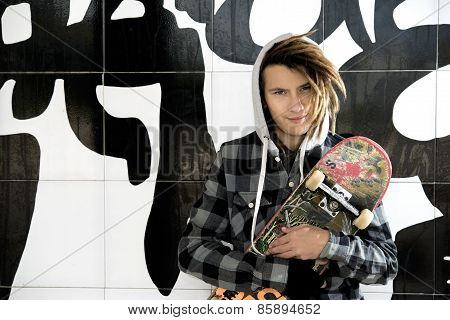 Portrait Of Young Guy With Skateboard And Rasta Hair