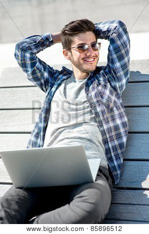 Portrait of young Man with laptop on the bench