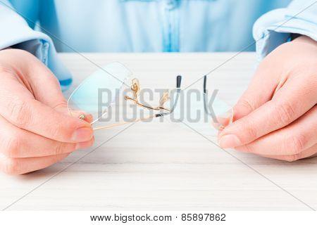 Hands holding old, broken glasses