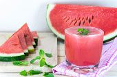 foto of mints  - Glass of fresh watermelon juice with mint leaves and sliced fruit on wooden table - JPG