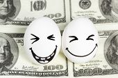 stock photo of priceless  - Two eggs with painted faces laughing at the a hundred dollar bill - JPG