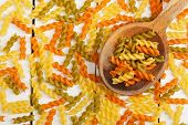 foto of ladle  - ladle with colorful fusilli pasta on old wooden table - JPG