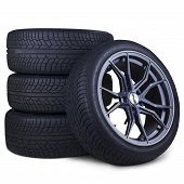 foto of four-wheel  - Closeup of four tires with racing rim and black texture isolated over white background - JPG