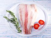 image of pangasius  - Pangasius fillet with herb and sliced cherry tomatoes on plate and color wooden table background - JPG