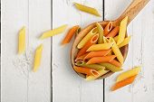 stock photo of ladle  - colorful penne pasta on wooden ladle closeup - JPG
