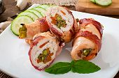 stock photo of bacon strips  - Delicious chicken rolls stuffed with green beans and carrots wrapped in strips of bacon - JPG