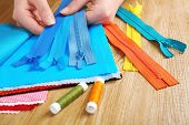 picture of zipper  - Colorful fabric samples and zipper in female hands on wooden table background - JPG