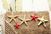 foto of sackcloth  - Sea stars on sackcloth on wooden background - JPG