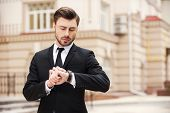 stock photo of watch  - Handsome young man in formalwear looking at his watch while standing at the street - JPG