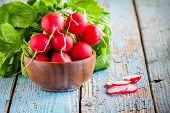 stock photo of radish  - bright fresh organic radishes with slices in the bowl on blue rustic table - JPG