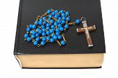 stock photo of rosary  - Blue rosary and black holy bible isolated on white background - JPG