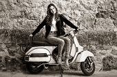 stock photo of vespa  - Young woman in urban background woman climb on a scooter motorcycle wearing casual clothes - JPG
