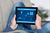 picture of screen  - man lying on a sofa and holding a tablet with program smart home on the screen - JPG