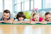 image of family bonding  - Happy family bonding to each other while lying on exercise mat in sports club - JPG