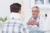 picture of neck brace  - Doctor talking to patient wearing neck brace in medical office - JPG