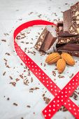 pic of bittersweet  - Dark chocolate and almonds decorated with red ribbon on white paper - JPG
