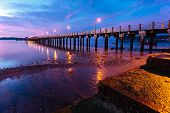foto of tide  - beautiful sunrise at the sea pier during tide - JPG