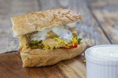 picture of flat-bread  - flat bread filled with chicken rice salad and yoghurt garlic dip on a rustic wooden table  - JPG