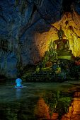 stock photo of cave woman  - A woman is praying in front of Buddha Image in cave - JPG