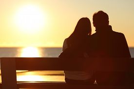 image of hug  - Back view of a couple silhouette hugging and watching sun on the beach - JPG