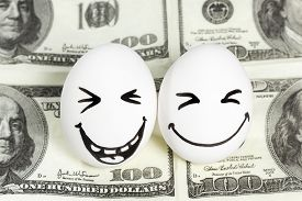picture of two dollar bill  - Two eggs with painted faces laughing at the a hundred dollar bill - JPG