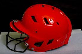 foto of fastpitch  - A orange Fastpitch batters helmet with a black face mask - JPG