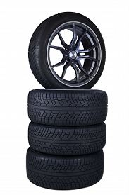 stock photo of four-wheel  - Closeup of four black tires stacked in the studio isolated over white background - JPG