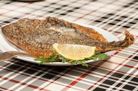 picture of flounder  - Fried flounder on a plate decorated with parsley and lemon - JPG