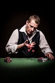 stock photo of gambler  - A male gambler rolls the dice in hopes to win - JPG