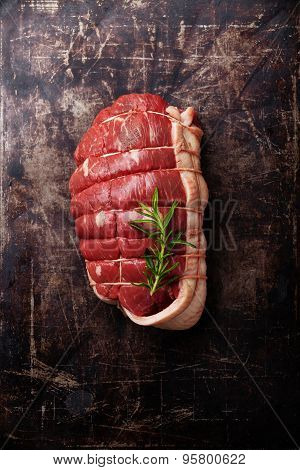 Roast Beef And Rosemary On Dark Metal Background