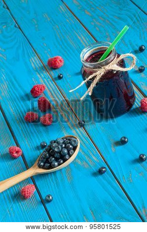 Mason jar with berries jam or marmalade and fresh raspberry, blueberry on a rustic wooden table. Coo