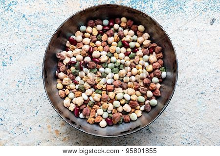 A iron bowl filled with nine types of protein rich grains on a plain background