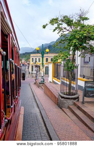 View from narrow alley covered by red and grey stones in the older part of Bogota city sorrounded by